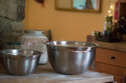 along with some mixing bowls with warm milk, yeast, and flour waiting